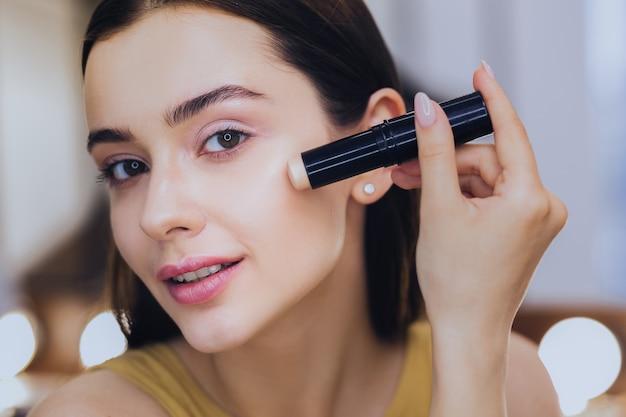 Concealer stick. charmante mooie vrouw met behulp van camouflagestift tijdens het aanbrengen van make-up