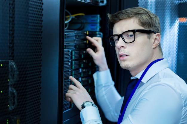 Concentratie. knappe vastberaden operator die in de buurt van apparatuur staat en eraan werkt