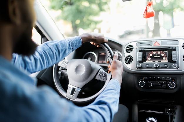 Concentreren op de weg. achteraanzicht van de jonge knappe afrikaanse man die recht kijkt tijdens het autorijden