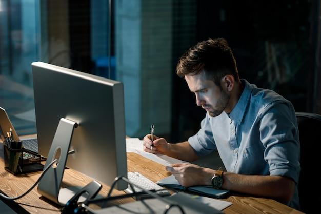 Concentrerende man laat werken met papieren