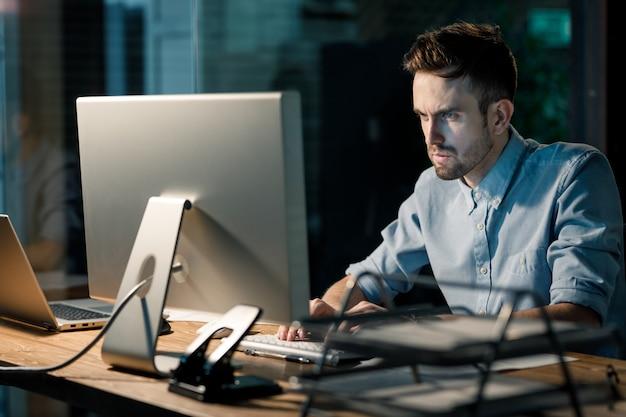 Concentrerende mens die met computer in bureau werkt