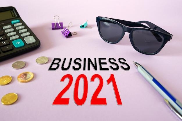 Concept: business 2021. rekenmachine, geld en glazen op tafel