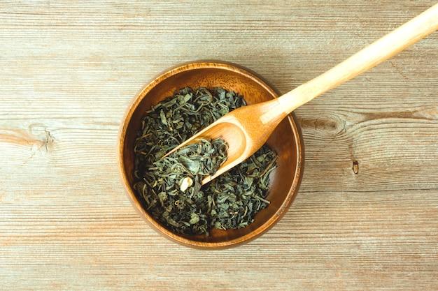 Concept chinese, japanse groene gedroogde theeblaadjes op bamboe lepel en ronde kom close-up op natuurlijke houten bovenaanzicht. tekst kopie ruimte