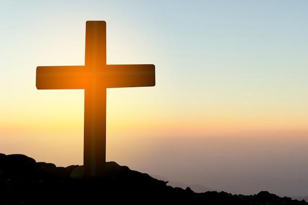 Concept conceptueel geel kruis religie symbool silhouet in de natuur over zonsondergang of zonsopgang hemel