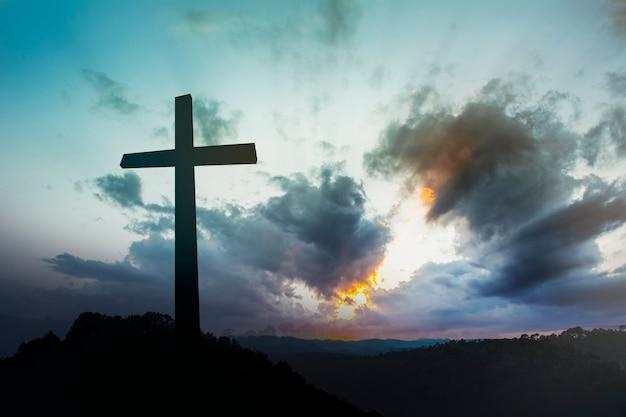 Concept conceptueel zwart kruis religie symbool silhouet in gras over zonsondergang of zonsopganghemel