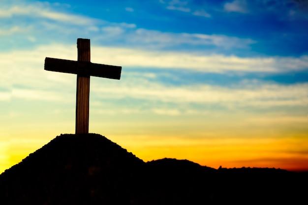 Concept conceptuele kruis religie symbool silhouet in de natuur over zonsopgang hemel