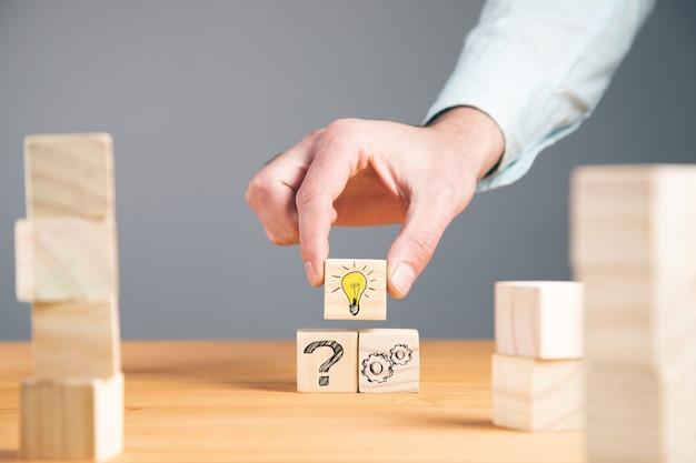 Concept creatief idee en innovatie. houten kubusblok in de hand met symbool