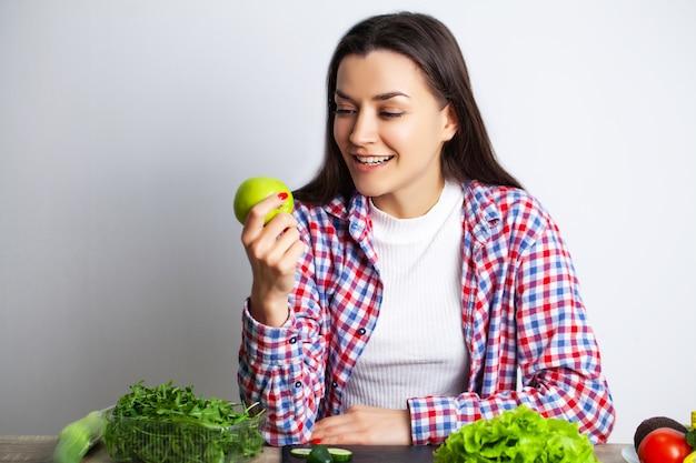 Concept dieet en gezond etend meisje met groenten op de achtergrond van de witte muur