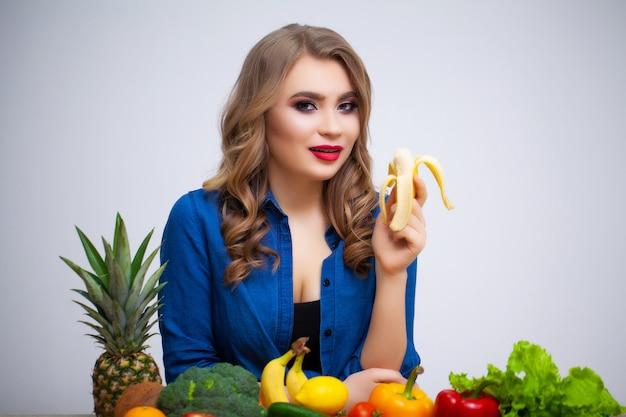 Concept dieet en gezond etende vrouw met groenten op witte muur