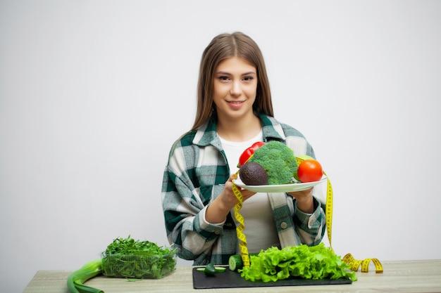 Concept dieet en gezonde etende vrouw met groenten op witte muurachtergrond