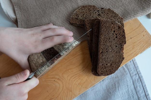 Concept eigengemaakt brood, natuurlijke landbouwproducten, binnenlandse productie. gezond en lekker biologisch eten. vrouw die vers gebakken volkorenbrood snijdt.