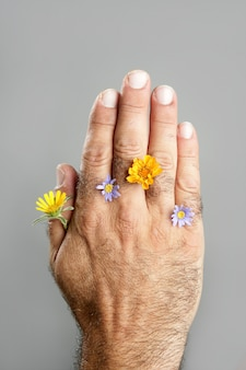 Concept en contrast van harige mensenhand en bloem