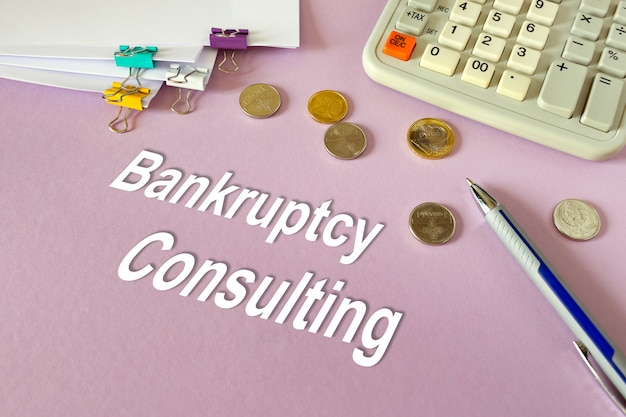 Concept: faillissementsadvies. rekenmachine, geld en documenten op tafel