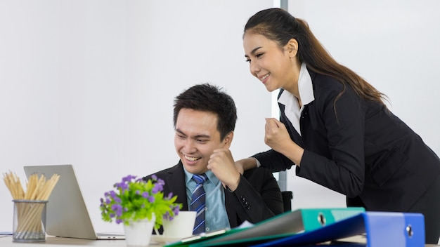 Concept felicitatie met succesvolle baan. aziatische kantoormensen zien er gelukkig en blij uit met werk. aziatische vrouw en man werknemer paar teamgenoot glimlachend en kijkend naar laptop voelen zich erg gelukkig op kantoor.