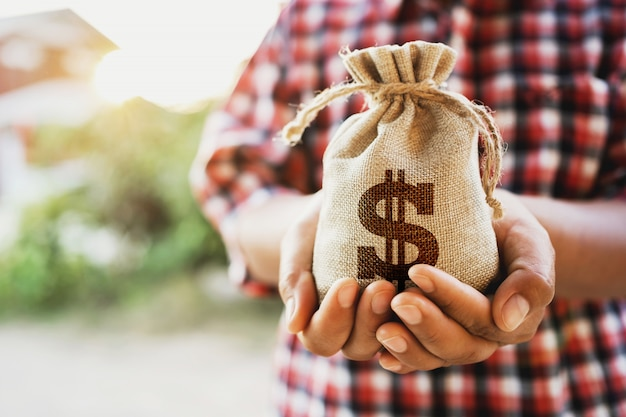 Concept financiële boekhouding. hand met geld tas