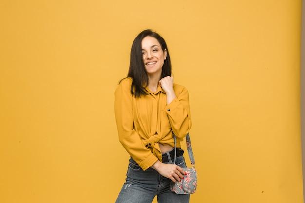 Concept foto van jonge vrouw met portemonnee, glimlachend en ziet er gelukkig uit. draagt geel shirt, geïsoleerde gele kleur achtergrond.