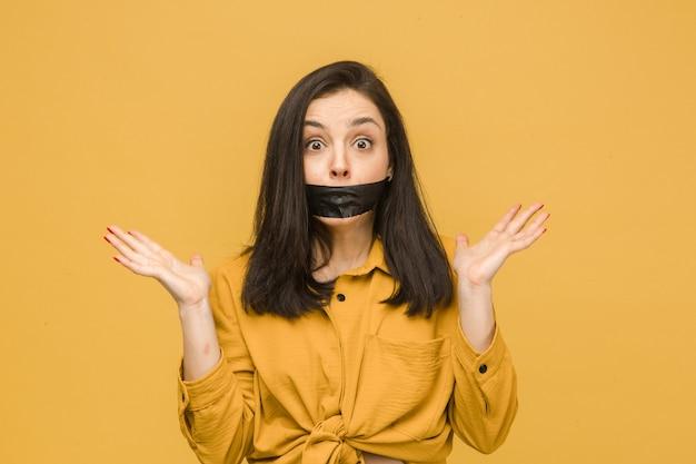 Concept foto van vrouwelijk slachtoffer met haar mond afgeplakt, houdt haar hoofd. draagt geel shirt, geïsoleerde gele kleur achtergrond.