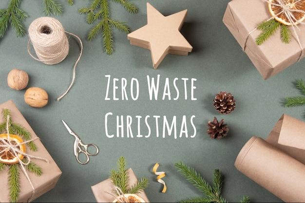 Concept geen afval vrolijk kerstfeest. dozen, ambachtelijk papier, touw, schaar, gedroogde sinaasappels en natuurlijk decor voor het verpakken van xmas, nieuwjaarsgeschenken op groene achtergrond. bovenaanzicht plat lag.