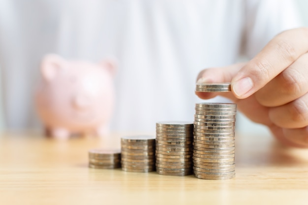 Concept geld besparen financiële zakelijke investeringen. de hand van mannetje die muntstukken zetten stapelt stap het groeien de groeewaarde met spaarvarken op