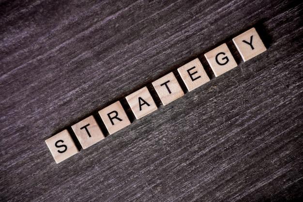 Concept gepresenteerd door kruiswoordraadsel met woorden strategie met houten kubussen