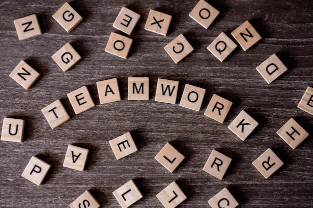 Concept gepresenteerd door kruiswoordraadsel met woorden teamwork met veel houten kubussen