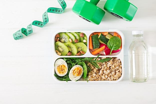 Concept gezond eten en sport levensstijl. vegetarische lunch. gezond ontbijt. goede voeding. lunchbox. bovenaanzicht plat leggen.