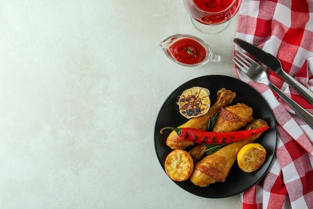 Concept heerlijk eten met gebraden kippentrommelstokken op witte geweven lijst