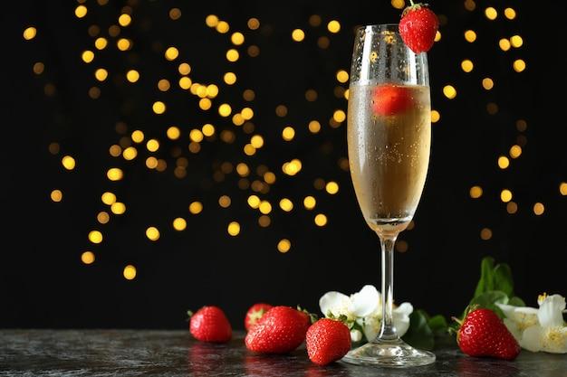 Concept heerlijke drank met rossini-cocktail tegen donkere achtergrond met vage lichten