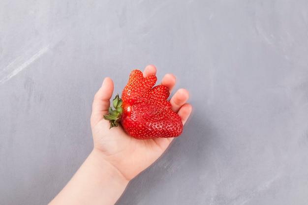 Concept - het eten van lelijke groenten en fruit. de hand van kinderen houdt een rijpe grappige aardbeien van ongebruikelijke vorm.