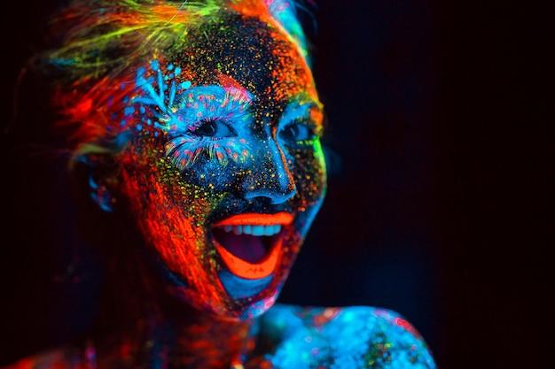 Concept. het meisje lacht. portret van een meisje geschilderd in fluorescerend poeder.