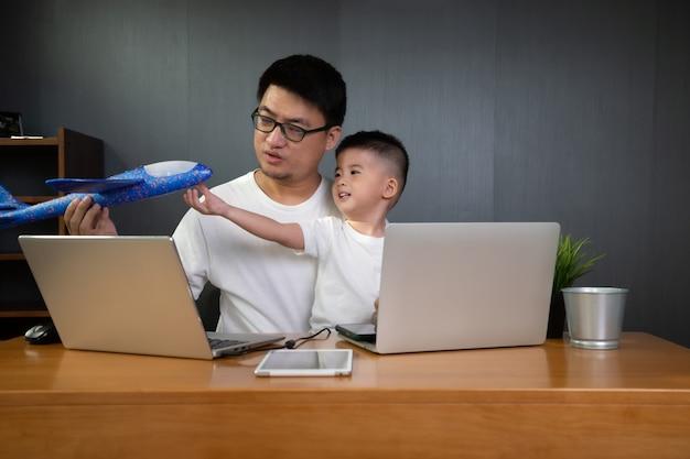 Concept het werk van huis met de aziatische mens die aan computerlaptop werken met zijn zoon