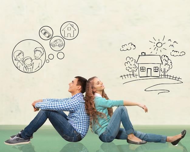 Concept. jong gelukkig familiepaar dat droomt van een nieuw huis, auto, kind, financieel welzijn