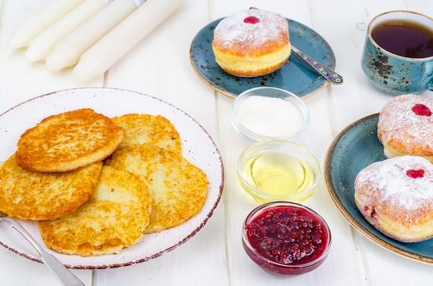 Concept joodse feestdag chanoeka. traditionele voedseldoughnuts en aardappelspannekoeken latkes.