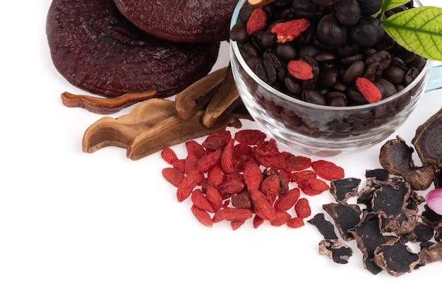 Concept koffie gemengd zwarte galingale, lingzhi en goji bessen kruiden voor gezondheid geïsoleerd op een witte achtergrond.