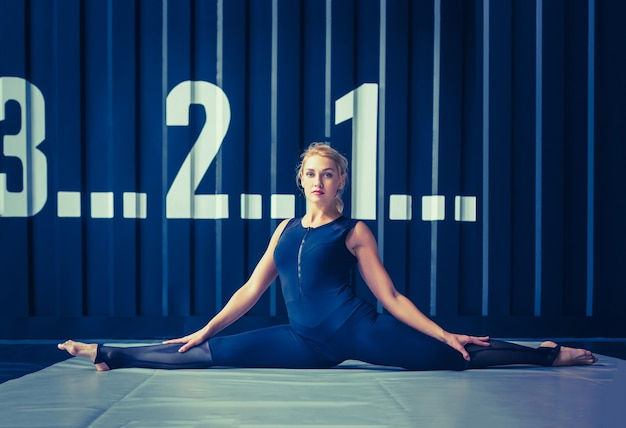 Concept: kracht, kracht, gezonde levensstijl, sport. krachtige aantrekkelijke gespierde vrouw crossfit-trainer die rekoefeningen doet of touw uitrekt tijdens training in de sportschool