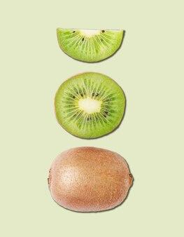 Concept lay-out gemaakt van vers gesneden kiwi en kiwi's op groene achtergrond. bovenaanzicht en macro.