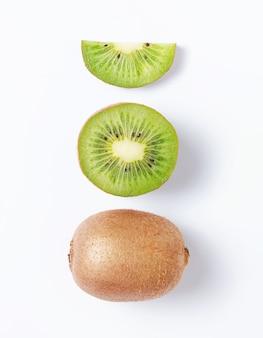 Concept lay-out gemaakt van vers gesneden kiwi en kiwi's op witte achtergrond. bovenaanzicht en macro. geïsoleerde foto