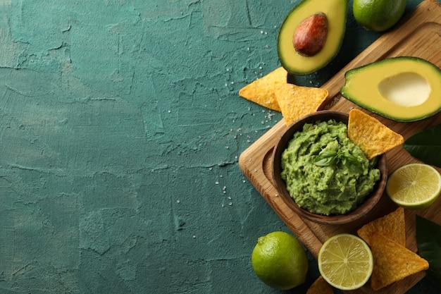 Concept lekker eten met kom guacamole op groene gestructureerde achtergrond