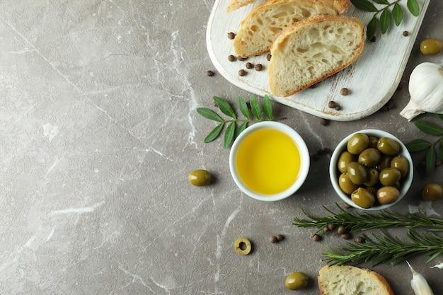 Concept lekker eten met olijfolie op grijze getextureerde tafel