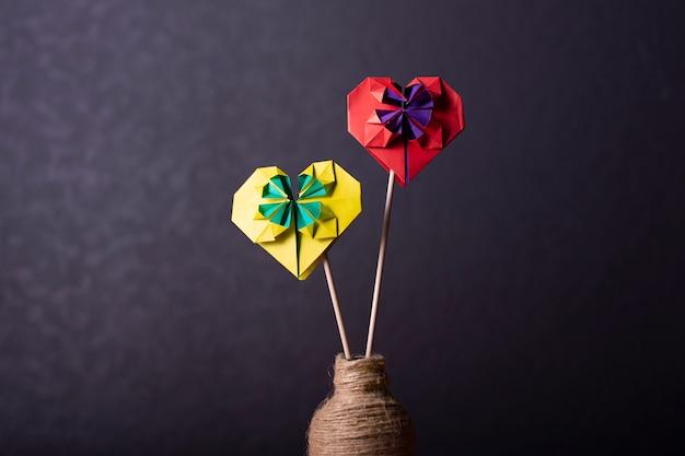 Concept liefde handgemaakte papercraft origami bewerkte gekleurd papier hart close-up shot in studio geel en rood