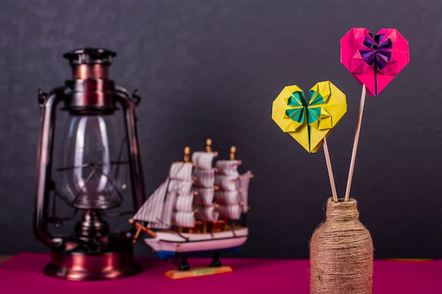 Concept liefde handgemaakte papercraft origami bewerkte gekleurd papier hart close-up shot in studio met lamp en boot