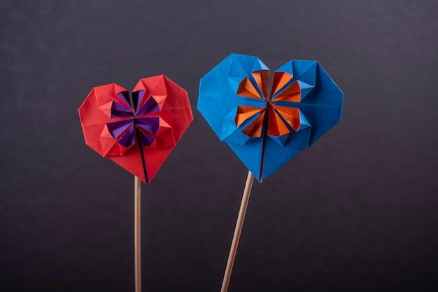 Concept liefde handgemaakte papercraft origami bewerkte gekleurd papier hart close-up shot op donkere muur