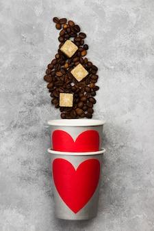Concept liefde voor koffie. grijze papieren bekers voor drankjes met rood hart, koffiebonen op een lichte achtergrond. bovenaanzicht voedsel achtergrond.