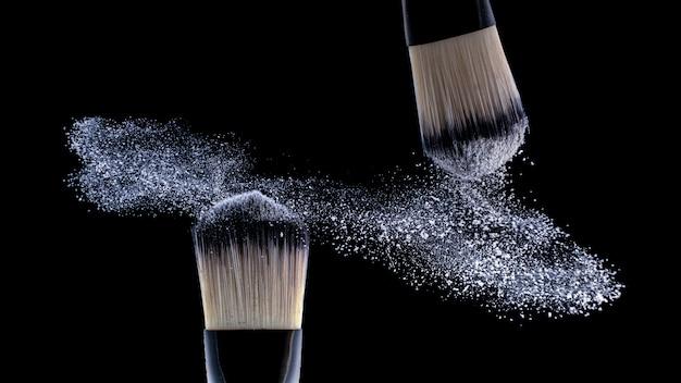 Concept, make-up. twee borstelmakers strooien poeder uit