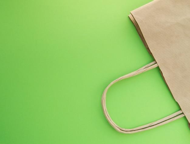 Concept nul afval, herbruikbare papieren zak om te winkelen, gratis plastic, groene achtergrond, bovenaanzicht