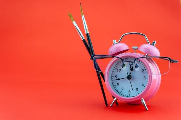 Concept onderwijs of bedrijf wekker en leraar bril bedrijfsobjecten geïsoleerd op kleurrijke achtergrond terug naar school concept