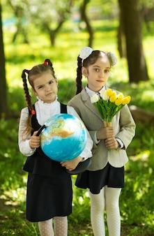 Concept - onderwijs. terug naar school. twee vrolijke blanke meisjesschoolmeisjes met bloemen en een wereldbol, blij om na de les in de klas naar huis terug te keren