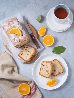 Concept ontbijt. versgebakken cake met rozijnen en sinaasappel op een snijplank en een blauwe achtergrond met fruitsinaasappels en een kopje thee. bovenaanzicht afbeelding