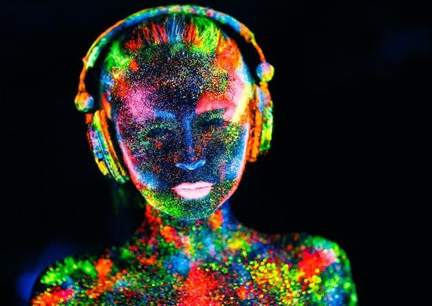 Concept. op het lichaam van een meisje geschilderd dj-deck. halfnaakt meisje geverfd in uv-kleuren.