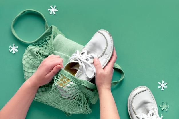 Concept plat lag met handen inpakken schoenen en kleding in netje. geef goederen op giving tuesday, deelnemen aan donatie-drive. verzamel ongewenste goederen en geef deze door aan diegenen die het nodig hebben.